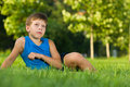 Boy imagines on the lawn a thoughtful is sitting in park Royalty Free Stock Image