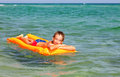 Boy on a inflatable mattress happy enjoying summer day floating in the sea Stock Photos