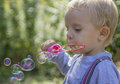 Boy inflates soap bubbles that glisten beautifully in the sun Royalty Free Stock Image
