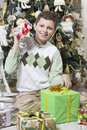 Boy is intrigued with christmas gifts young many Stock Images