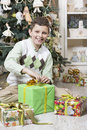 Boy is intrigued with christmas gifts young many Stock Photography