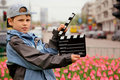 Boy in jacket and cap with cinema clapper board Royalty Free Stock Photo