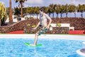 Boy jumping in the blue pool has fun outdoor Stock Photo