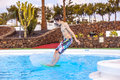 Boy jumping in the blue pool has fun outdoor Stock Photography