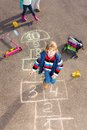 Boy jumping on hopscotch the game drawn the asphalt looking up Stock Image
