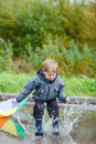 Boy jumping in puddle Stock Images