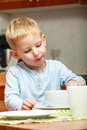 Boy kid child eating corn flakes breakfast meal at the table blond morning home Royalty Free Stock Image