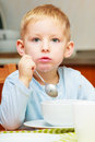 Boy kid child eating corn flakes breakfast morning meal at home happy childhood blond cereal with milk the kitchen table indoor Stock Photos