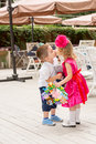 The boy kid gives flowers and kissing girl child on birthday. Royalty Free Stock Photo