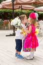 The boy kid gives flowers to girl child on birthday Royalty Free Stock Photo