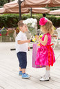 The boy kid gives flowers to girl child on birthday. Royalty Free Stock Photo