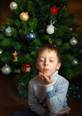 Boy is kissing and christmas tree kiss of near Royalty Free Stock Photos