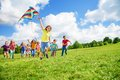 Boy with kite and friends running large group of boys girls running after Royalty Free Stock Image