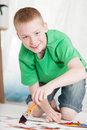 Boy kneeling on painting while holding brush in green shirt and blue jean shorts against a light background Stock Photos