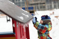 Boy knocks icicles at playground in winter Royalty Free Stock Photography
