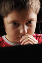 Boy at laptop closeup in red with serious expression photo Stock Photography