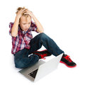 Boy with laptop computer a shocked pre teen tousled hair sitting in front of a looking at its screen awe and terror Royalty Free Stock Photos