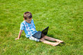 Boy with laptop sitting on the grass little using outdoors Stock Image