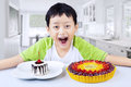 Boy laughing with desserts at home fruit Stock Image