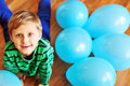 Boy laying on the wooden floor with blue balloons Royalty Free Stock Photos