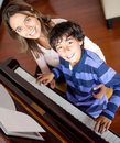 Boy learning to play piano Stock Photos