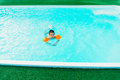 Boy learning to swim in pool with arm floats Stock Photos