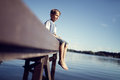 Boy with legs dangling from pier Royalty Free Stock Photo