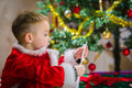 Boy and letter adorable year old check over him to santa claus christmas tree on background Stock Image