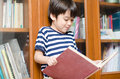 Boy in library holding book studying Royalty Free Stock Photo