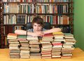 Boy in library young teenage with big pile of books Stock Photography