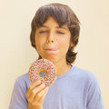 Boy licking his lips at sweet donut teen caicasian Royalty Free Stock Photos