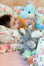 Boy lies in bed with soft toys Stock Image
