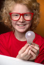 Boy with a light bulb cheerful red hair in glasses holding and smiling at camera Stock Photos