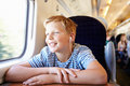 Boy listening to music on train journey smiling Royalty Free Stock Image