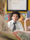 Boy listening to teacher reading in class elementary schoolboy classroom Stock Photography