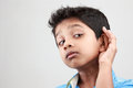 A boy listens to low voice keen on listening with hands on his ears Stock Photo