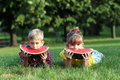 Boy and little girl eat watermelon lying on grass Royalty Free Stock Photos