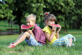 Boy and little girl eat watermelon sitting on grass Stock Image