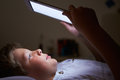 Boy looking at digital tablet in bed at night lying down Royalty Free Stock Images