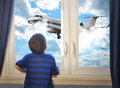 Boy looking at flying airplane in room a young is out of the window a big through the sky for a travel concept Royalty Free Stock Photos