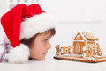 Boy looking at gingerbread house wearing santa hat closeup Stock Photo