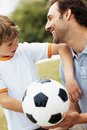 Boy looking at his smiling father holding football Stock Image