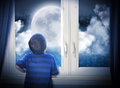 Boy looking at night moon and stars a young is out of the window a big in the dark with space for an astronomy or imagination Royalty Free Stock Images