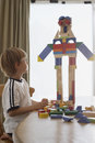 Boy looking at robot made of blocks on table side view little home Royalty Free Stock Photography