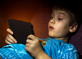The boy is looking at the screen of the tablet pc watching with delight Royalty Free Stock Photography