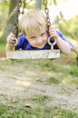 Boy looking through swing and smiling young the chains on a white weathered wooden Royalty Free Stock Images