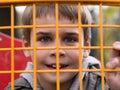 Boy looking through yellow metal net Royalty Free Stock Photo