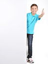 Boy looks out from the white banner with thumbs up gesture full portrait of cheerful isolated on background Stock Photography