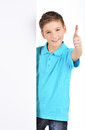 Boy looks out from the white banner with thumbs up gesture portrait of cheerful isolated on background Stock Images