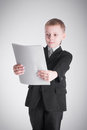 Boy looks on paper in a business suit Royalty Free Stock Photo